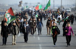 Shiite Muslim pilgrims carrying religious banners walk through a main road in Baghdad on their way to the shrine central city of Karbala on December 9, 2014 where they take part in the Arbaeen religious festival. Arbaeen marks the 40th day after Ashura which commemorates the seventh century killing of Prophet Mohammed's grandson, Imam Hussein. The holy Iraq city of Karbala sees millions of Shiite visitors every year over the 40-day period of mourning that follows the annual commemoration of the death of Imam Hussein, who was slain by the forces of the caliph Yazid in 680 AD. AFP PHOTO / AHMAD AL-RUBAYE